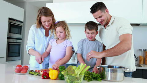 Smiling family preparing a healthy dinner together Footage