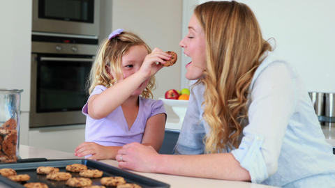 Little girl having milk and cookies with her mothe Footage