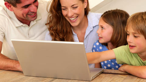 Smiling family using laptop together at table Footage