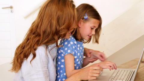Little girl using laptop with her pretty mother at the table Footage