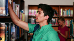 Handsome student picking out a book in the library Footage
