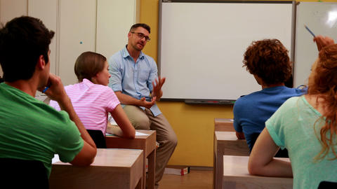 Lecturer sitting and speaking to his students in classroom Footage