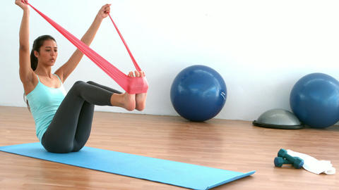 Fit brunette stretching using resitance band in studio Footage