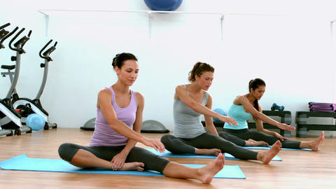 Fit women doing yoga together in studio Footage