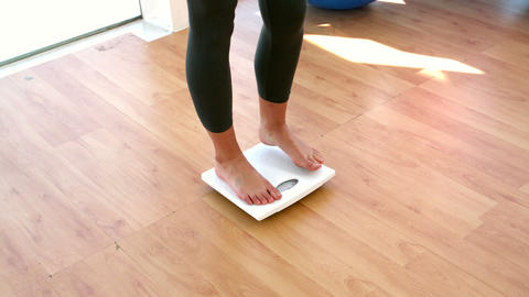 Woman stepping on scales Footage