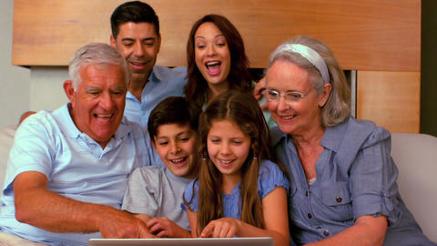 Extended family using laptop together on couch Footage