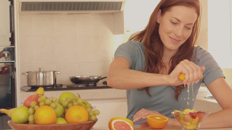 Woman squeezing orange over her fruit salad Footage