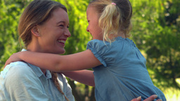 Young mother giving her daughter a hug in the park Footage