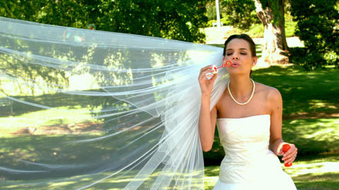 Bride blowing bubbles in the park Footage