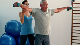 Elderly man lifting hand weights with physiotherapist Footage