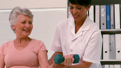 Physiotherapist helping patient lift hand weight Footage