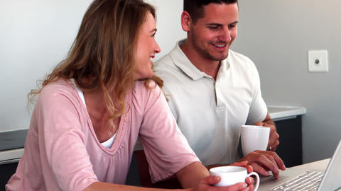 Happy Couple Having Coffee And Using Laptop In Kit stock footage