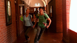 Happy students running through a hallway Footage