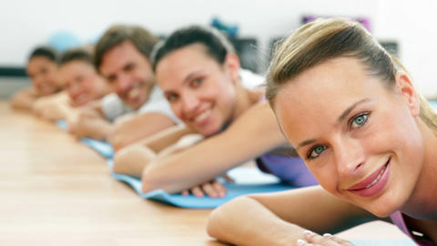 Fitness class lying on mats smiling at camera Footage