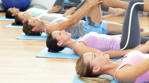 Pilates class lying on mats stretching Footage