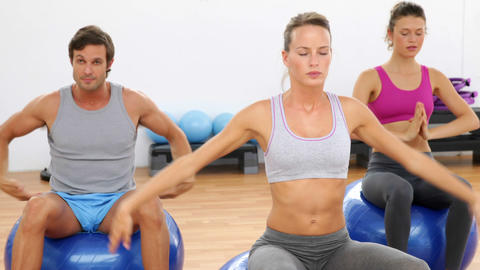 Fitness class sitting on exercise balls stretching Footage