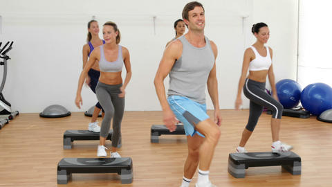 Aerobics class stepping and clapping together Footage