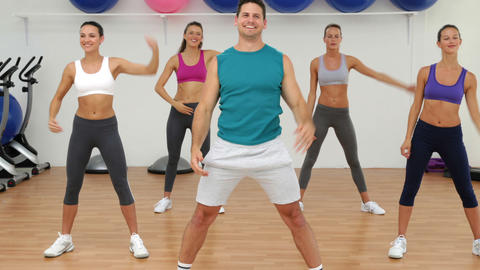Aerobics class stretching together led by instructor Footage
