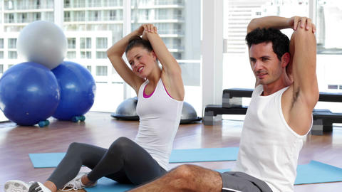 Couple stretching arms together on exercise mat Footage