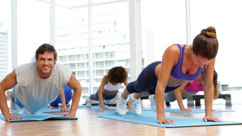 Fitness class doing push ups together on exercise mats Footage