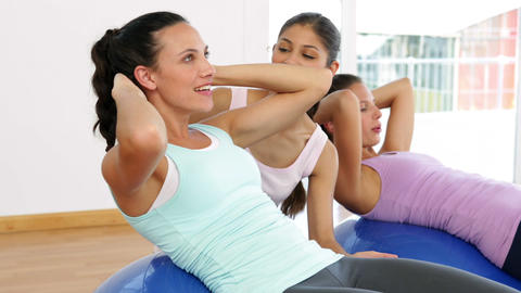 Trainer helping client do sit ups on exercise ball Footage
