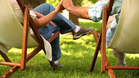 Retired couple sitting in deck chairs holding hand Footage