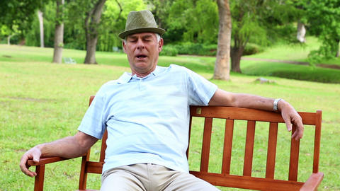 Retired man dozing on a park bench Footage