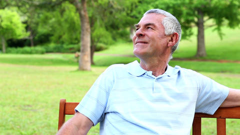 Retired man relaxing on a park bench Footage