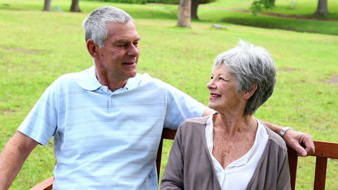 Retired couple sitting on a park bench talking Footage