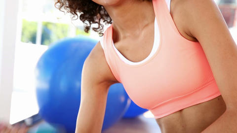 Fit woman lifting dumbbells and smiling at camera Footage