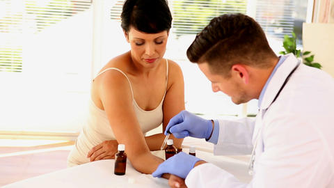 Dermatologist applying ointment to womans arm Live Action