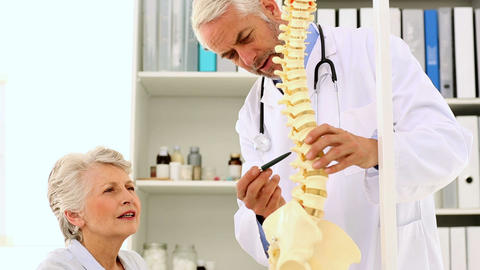 Doctor Explaining A Spine Model To Patient stock footage