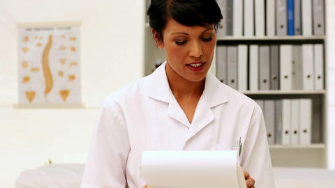 Nurse writing on clipboard Footage