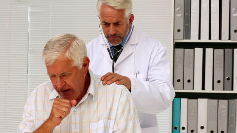 Doctor examining his senior patient who has a coug Footage