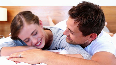 Happy couple lying on bed and laughing Footage