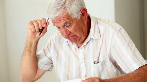 Senior man sitting at table working out bills Footage