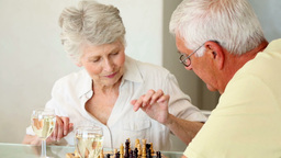 Senior couple sitting at table playing chess Footage