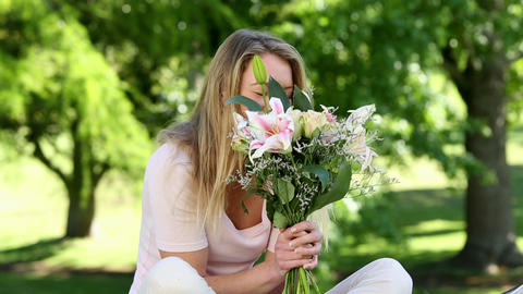 Pretty girl smelling bouquet of flowers in the par Footage