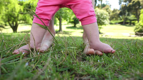 Baby walking on mothers feet on the grass Footage