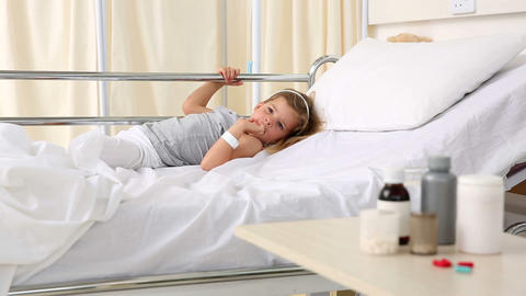 Little girl lying in hospital bed looking at medic Footage