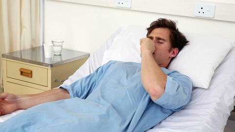 Sick man lying on hospital bed coughing Footage