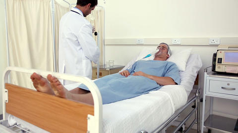 Doctor checking patient in bed with an oxygen mask Footage