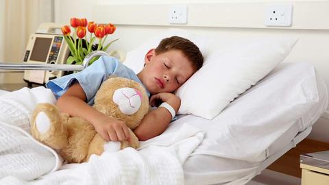 Little sick boy sleeping in bed with teddy bear Footage
