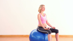 Pregnant blonde meditating on exercise ball Footage
