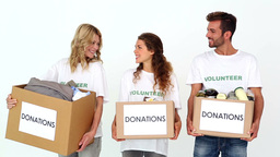 Team of volunteers smiling at camera holding donations boxes Footage