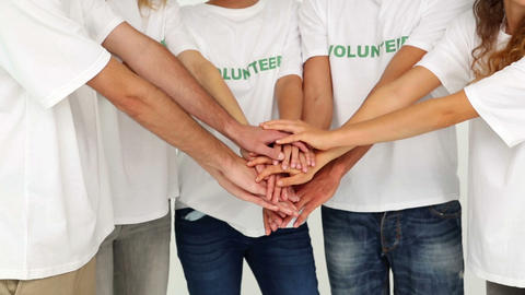 Team of volunteers putting hands together Footage