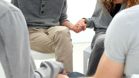 Rehab group sitting in a circle holding hands Footage