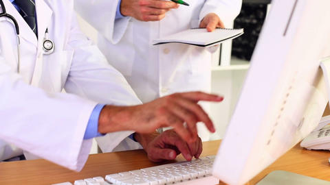 Doctors Discussing Something On Computer Screen stock footage