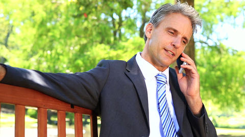 Businessman sitting on park bench talking on phone Footage