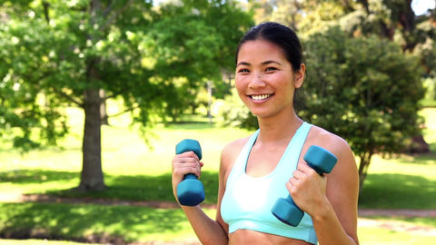 Fit asian girl lifting dumbbells Footage